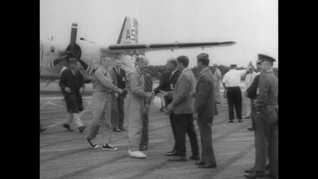 stockvideo's en b-roll-footage met nasa staff on runway awaiting arrival of astronauts tom stafford and gene cernan by plane / plane arrives / stafford and cernan cross runway shake... - hatch