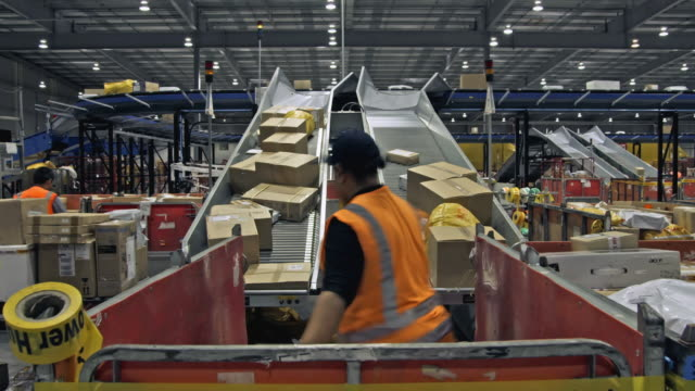 t/l ws staff taking sorted parcels from chute and stacking in crate, auckland, new zealand - distribution warehouse stock videos & royalty-free footage