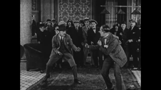 vídeos de stock, filmes e b-roll de 1924 staff try to stop men fighting in crowded hotel lobby - preto e branco