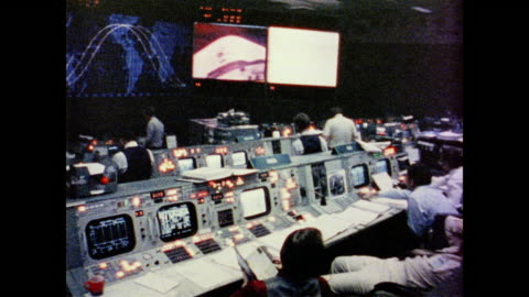 staff work busily at control panels, computers and work stations throughout the control room - 1981 stock videos & royalty-free footage
