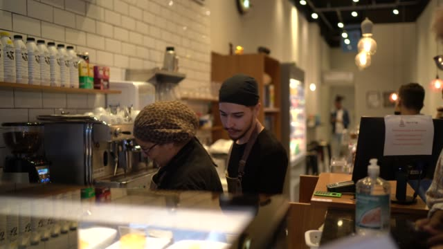 staff working behind counter in busy coffee shop - candid stock videos & royalty-free footage