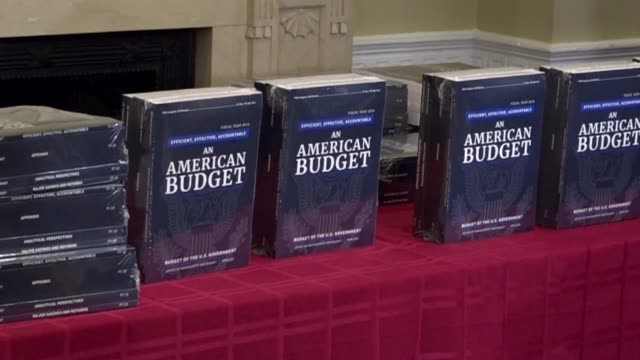 Staffers unpack copies of the fiscal 2019 budget request of the Trump administration to Congress entitled An American Budget as media look on Muted...