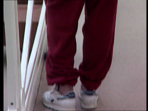 stockvideo's en b-roll-footage met staffordshire werrington juvenile centre int bv prison guard away along landing tcs prisoner's feet in trainers tilt up to bv young man standing next... - number 9