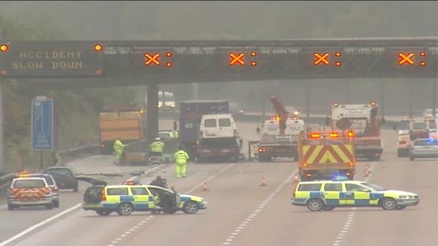 stag weekend motorway crash: groom speaks out; england: surrey: m25 motorway: ext workmen clearing up wreckage in aftermath of motorway crash in... - m25 video stock e b–roll