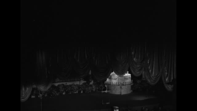 WS stage at the Pantages Theatre with VO dramatic music as curtain rises to reveal a giant birthday cake decorated with little lighted Oscar...