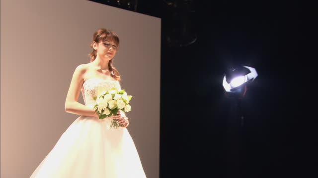 MS Stage light and wall/ PAN model in strapless dress holding flowers walking on catwalk, turning around, and walking back/ London, England