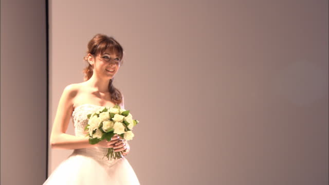 ms stage light and wall/ pan model in strapless dress holding flowers walking on catwalk, turning around, and walking back/ london, england - この撮影のクリップをもっと見る 1064点の映像素材/bロール