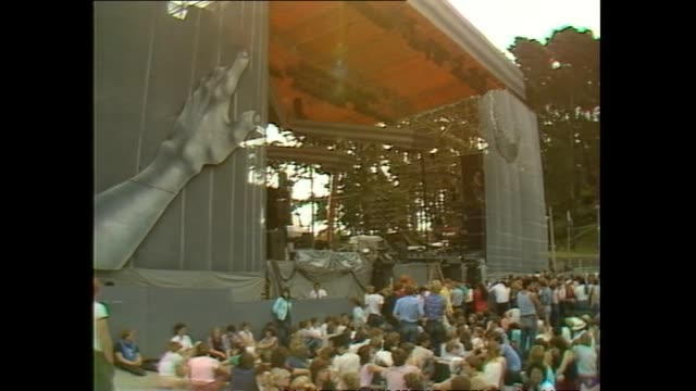stockvideo's en b-roll-footage met stage preparations prior to 1983 david bowie concert at western springs stadium in auckland with member of road crew reclining in hammock as crowd... - david bowie