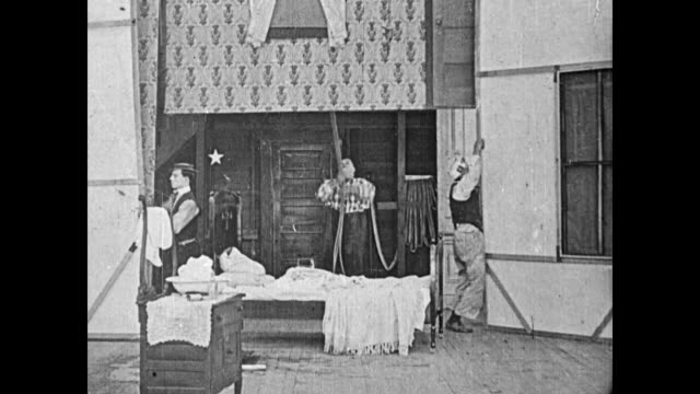 1919 Stagehands (Buster Keaton, Fatty Arbuckle, and Al St John), remove backdrops and bedroom props from a vaudeville stage with Keaton acting as boss