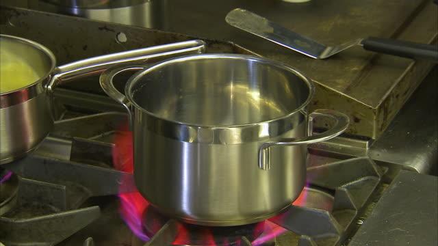 vídeos de stock, filmes e b-roll de stainless casserole on a flaming hot stove - fogão
