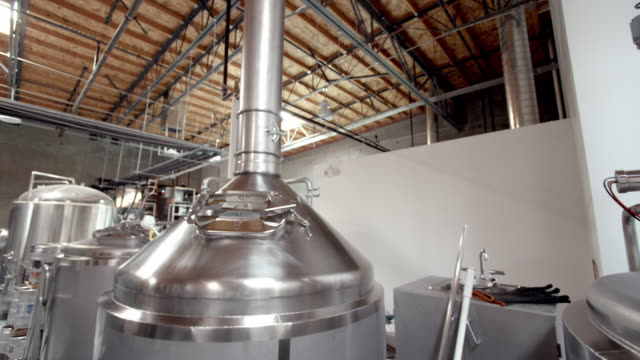 ds stainless steel boil kettle in modern micro brewery next to whirl pool tank / thousand palms, california, usa - 醸造所点の映像素材/bロール
