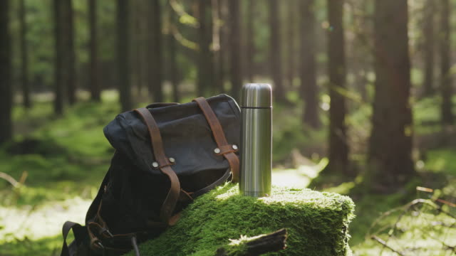 a stainless steel coffee thermos and a backpack in a forest - coffee break stock videos & royalty-free footage