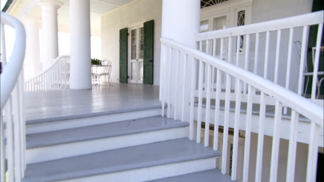 A staircase climbs to the balcony of a plantation house Available in HD.