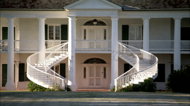 Staircases curve around the doorway of the Evergreen Plantation house. Available in HD.
