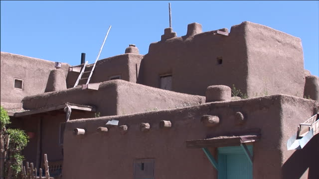 stairs lead up to a small porch on the front of an adobe building in taos pueblo. - new mexico stock-videos und b-roll-filmmaterial