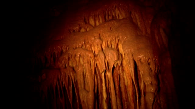 stalactites hang from cave walls. - calcium carbonate stock videos and b-roll footage