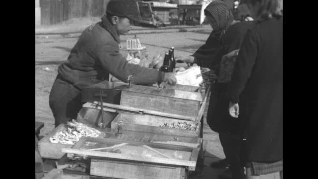 stalin prospect in mukden / street vendors with items for sale / aerial pan of a central park with snow on ground / soviet headquarters / vs train... - manchuria stock videos & royalty-free footage