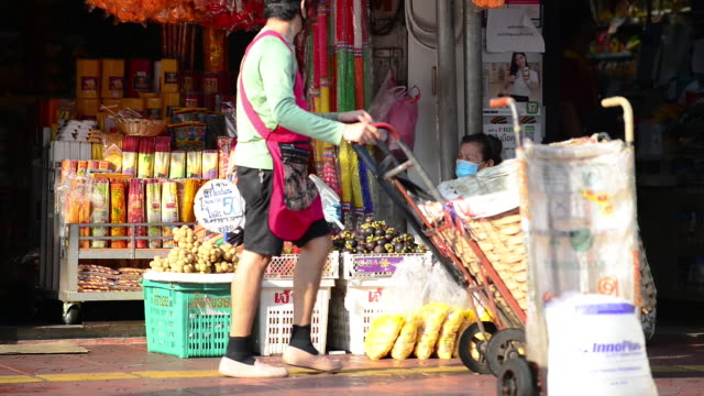 stall owner wearing face shield and face mask talking to each other - market stall stock videos & royalty-free footage