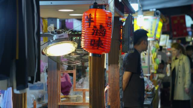stallholder looking at crowds in raohe night market - taiwan stock videos & royalty-free footage