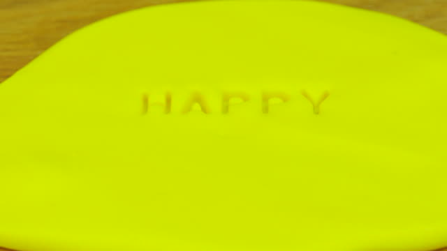 Stamp 'Happy New Year' on yellow fondant . Front view.