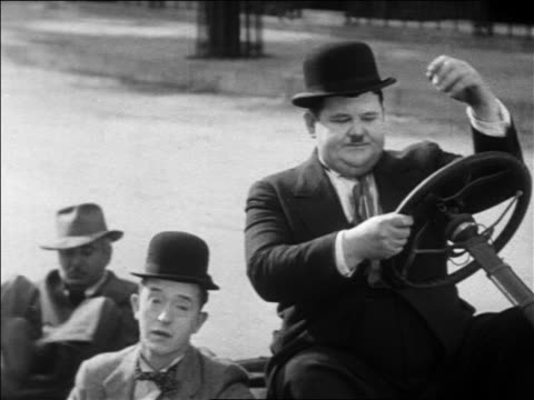 vidéos et rushes de stan laurel oliver hardy sitting in collapsed car / man getting up in background / feature - 1931