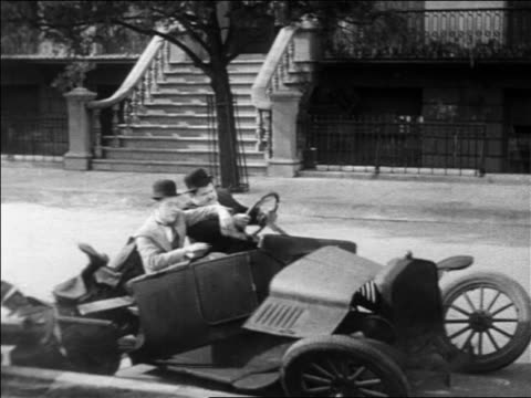 Stan Laurel Oliver Hardy sitting in convertible car with man / car collapses / feature