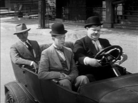 Stan Laurel Oliver Hardy sitting in convertible car with man in backseat / feature
