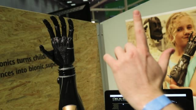 A stand host demonstrates a robotic prosthetic arm developed by UK startup Open Bionics mimicking his finger movements at the CUBE Tech Fair for...