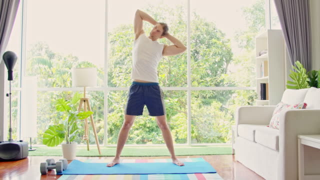 stand up and stretch that hip and center core. - exercise room stock videos & royalty-free footage