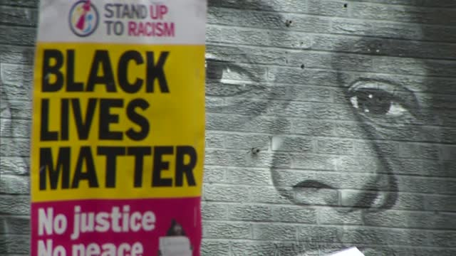 stand up to racism protest at marcus rashford mural; england: manchester: withington: ext people giving speeches to crowd of protesters in front of... - giving stock videos & royalty-free footage