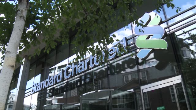pan standard chartered sign and logo on exterior of office building / pull focus shots of logo tree branches in foreground / tilt down sign and... - newly industrialized country stock videos and b-roll footage