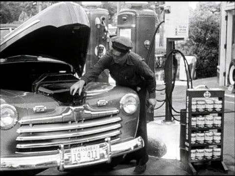 service station standard oil attendant in uniform checking engine oil level under hood of 1946 ford convertible opening quart can of 'permalube'... - 1946 stock videos and b-roll footage