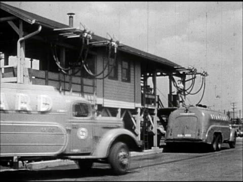 standard' oil gas delivery tank truck pulling in behind another truck at company refueling station, man on raised platform w/ filling hoses.... - routine stock videos & royalty-free footage