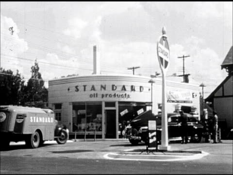service station ws 'standard' oil gas delivery tank truck pulling into filling station car being serviced at pump later amoco americana fossil fuel... - routine stock videos & royalty-free footage