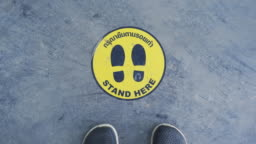 POV Standing and walking on queue social distancing sign.