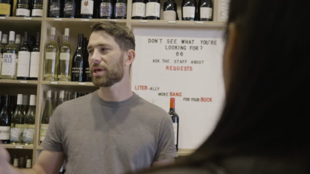 stockvideo's en b-roll-footage met standing at the checkout counter of neighborhood market and wine shop, a caucasian male business owner talks with a young a korean american woman. - werkneemster