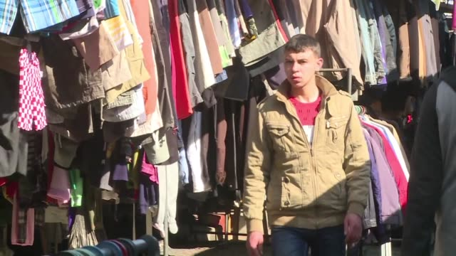 standing by skips full of clothes vendors call out to bargain hunters scrambling for the not so latest styles in the gaza strip - scrambling bildbanksvideor och videomaterial från bakom kulisserna
