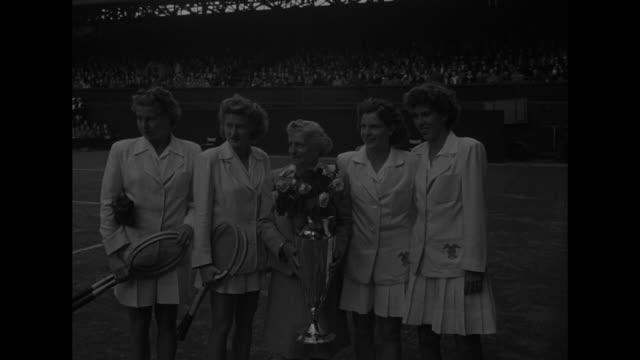 Standing for photo opportunity on court at Wimbledon winning US team left to right Pauline Betz Margaret Osborne Louise Brough and Doris Hart Hazel...
