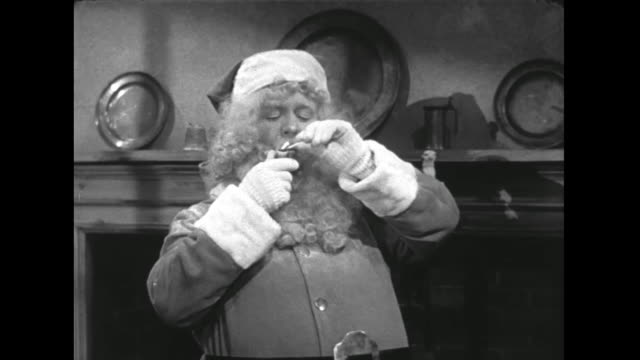 1946 Standing in front of fireplace, Santa lights his smoking pipe