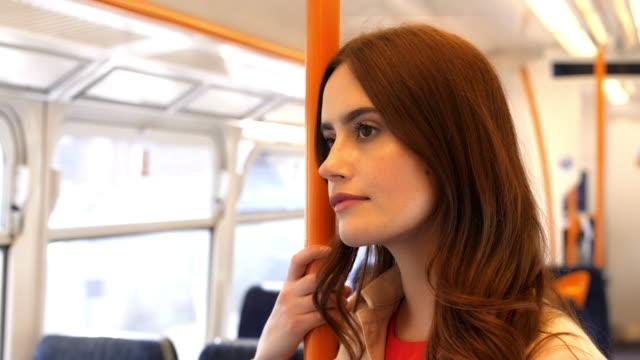 standing on a train on the go. beautiful young woman. - treno pendolare video stock e b–roll