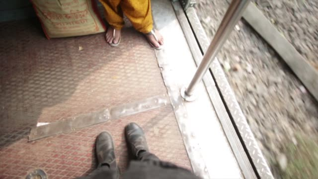 pov standing on moving train in india - stillstehen stock-videos und b-roll-filmmaterial
