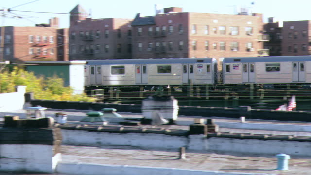 POV Standing on rooftop watching elevated train go by / New York City, New York, United States