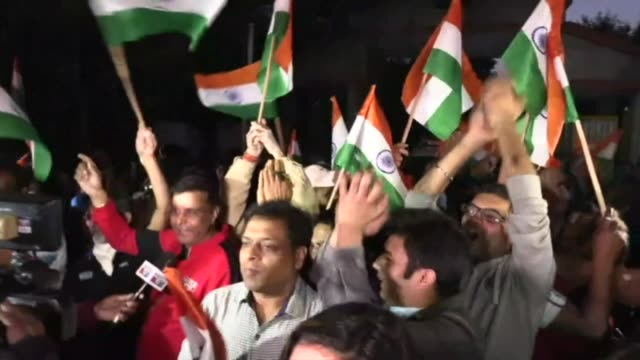 standing outside tihar jail in delhi, people wave indian flags and cheer after four men were executed for the gang-rape and murder of a woman on a... - sexual violence stock videos & royalty-free footage