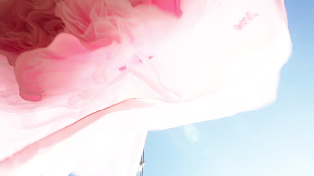 standing under vintage pink cocktail dress with blue sky in background - tulle stock videos and b-roll footage