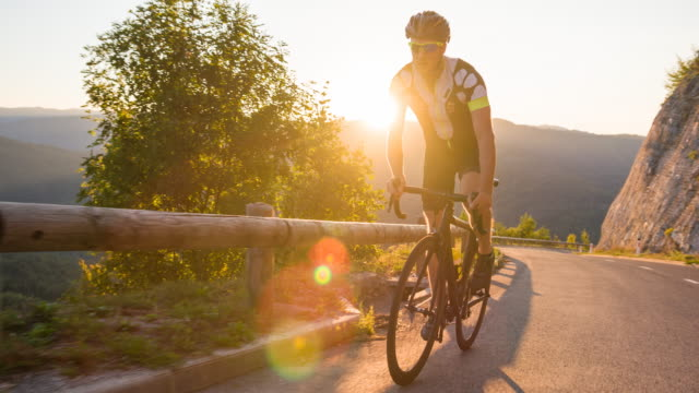 standing while road cycling uphill at sunset - triathlon stock videos & royalty-free footage