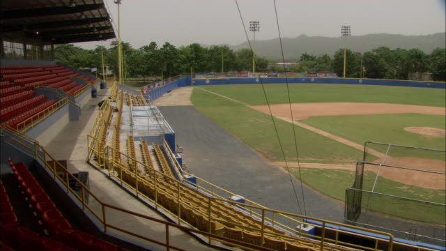 vídeos y material grabado en eventos de stock de pan/reverse empty diamond w/ dirt base paths amp pitching mound batting cage rows of seats blue outfield wall trees amp mountains bg sports athletics... - base home