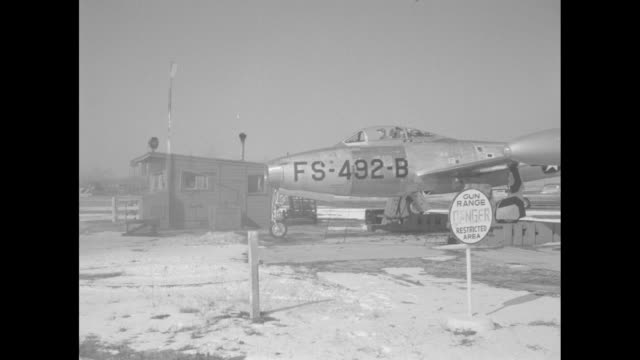 WS F84 stands on snowy airfield with spent shell casings on ground beneath it smoke emerges as gun fires for test / worker in cockpit starts the...
