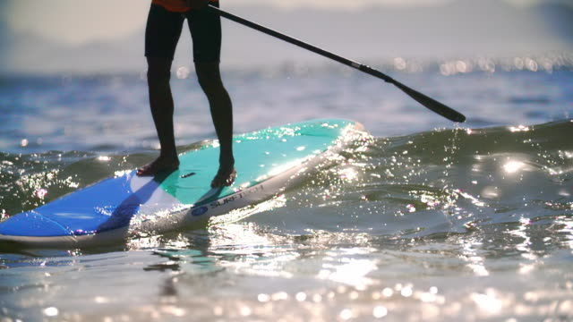 Stand-up paddleboarder rises and balances on wave breaking on Copacabana Beach in slow motion