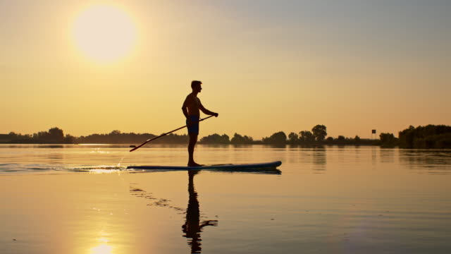 slo mo stand-up paddleboarding at sunset - recreational pursuit stock videos & royalty-free footage
