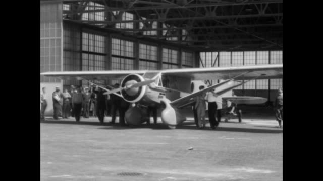 / stanislaus hausner shakes hands with his wife martha as he prepares to board his biplane, santa rosa maria, for his transatlantic flight to poland... - pilot stock videos & royalty-free footage